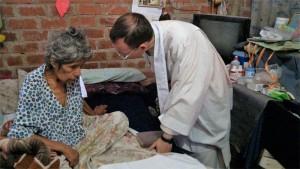 Con los enfermos: un sacerdote de la Unión Lumen Dei atiende a una enferma en las misiones del Perú.