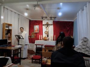 Fotografía de un sacerdote de la Unión Lumen Dei predicando durante una vigilia de adroación