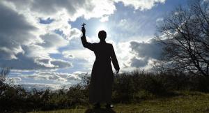 Foto en la que posa un seminariata misionero de la Unión Sacerdotal Lumen Dei en un lugar campestre, alza su cruz misionesra teniendo como fondo el cielo con las nubes iluminadas por el sol